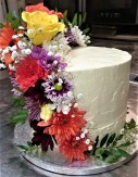 Lustrous Lemon - 3 layers of lemon drizzle, filled with lemon curd and lemon buttercream frosting. Decorated with fresh seasonal flowers. Serves around 23. £89.50